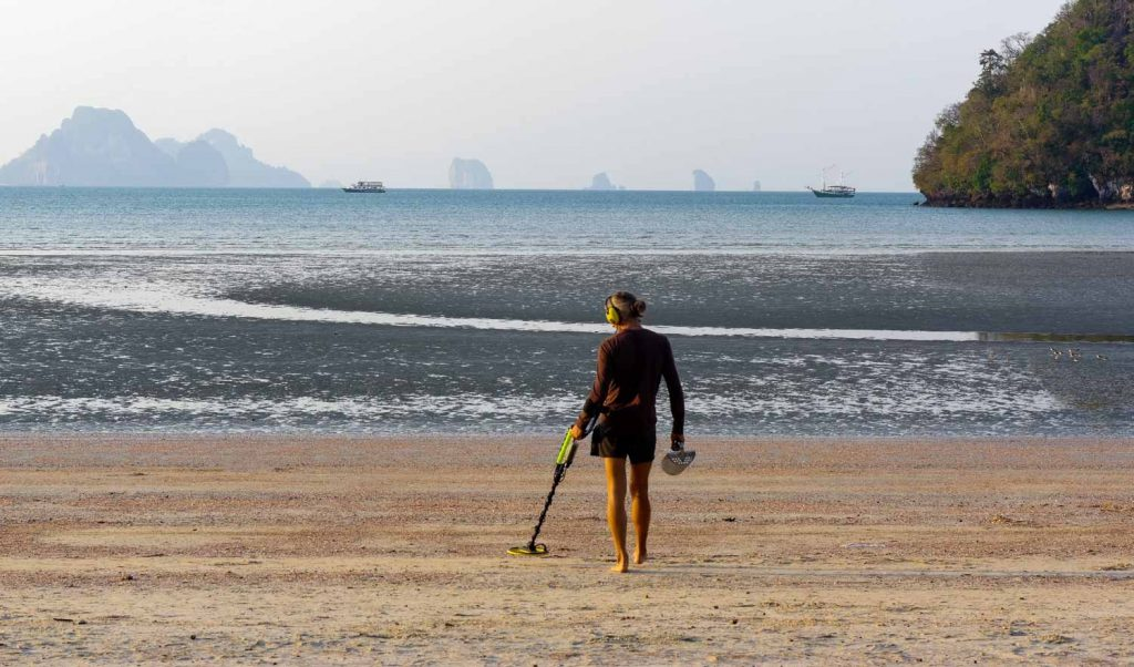 Person with a metal detector looking for valuables on a beach.